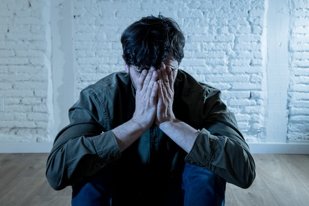 young depressed man sitting against a white wall at home with a shadow on the wall feeling miserable, lonely and sad in mental health depression concept Stock Photo