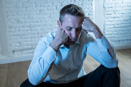 depressed business man feeling sad, lonely and suffering from anxiety leaning on a white wall at home in mental health depression concept Stock Photo