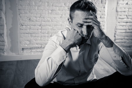 depressed business man feeling sad, lonely and suffering from anxiety leaning on a white wall at home in mental health depression concept