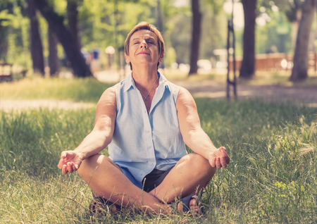 Yoga at park. Senior woman in a meditative yoga pose sitting on green grass. Concept of calm and meditation.
