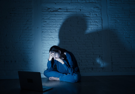 Sad and scared female Young woman with computer laptop suffering cyberbullying and harassment being online abused by stalker or gossip feeling desperate and humiliated in cyber bullying concept. Stock Photo - 105730321