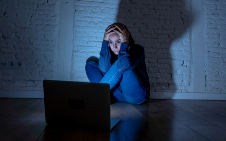 Sad and scared female Young woman with computer laptop suffering cyberbullying and harassment being online abused by stalker or gossip feeling desperate and humiliated in cyber bullying concept. Фото со стока
