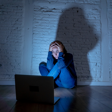 Sad and scared female Young woman with computer laptop suffering cyberbullying and harassment being online abused by stalker or gossip feeling desperate and humiliated in cyber bullying concept. Stock Photo