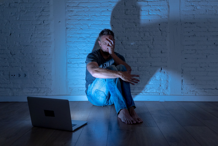 Severely distraught young men with computer laptop suffering cyberbullying and harassment being online abused by stalker or gossip feeling desperate and humiliated in cyber bullying concept. Stock Photo - 105730642