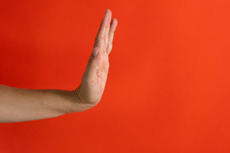 Studio photo of a woman hand showing stop gesture and sign isolated on a red background in rejecting stopping concept.