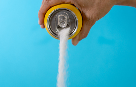 Hand holding soda can pouring lots of sugar in metaphor of sugar content of a refresh drink in healthy nutrition, diet, sweet and carbonated drinks addiction and unhealthy food concept.