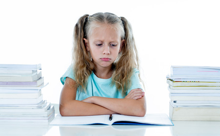 Frustrated little schoolgirl feeling a failure unable to concentrate in reading and writing difficulties learning problem attentional disorders special needs and low academic performance concept. 免版税图像