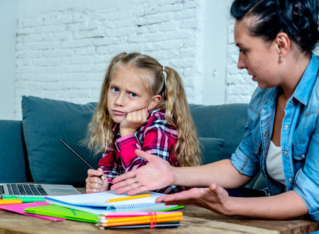 Mother Becoming Frustrated With Daughter Whilst Doing Homework Sitting On Sofa At Home Stock Photo