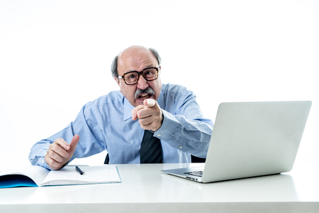 60s senior businessman boss furious shouting and gesturing upset and mad sitting on desk in Managing and Stress Problems at Work isolated on white background.