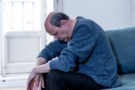 Overwhelmed old senior man suffering alone at home feeling confused sad alone on couch at home in Aging Retirement widower Dementia and Alzheimer concept. Stock Photo