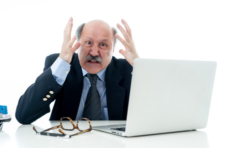 Angry and tired mature businessman overworked at desk not understanding laptop in Older adults perception and use of technology Overtime stress and overwork concept isolated in white background Stok Fotoğraf - 109717321