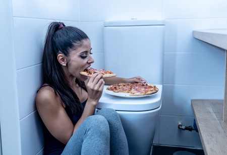 Attractive young and sad bulimic young woman feeling guilty and sick eating while sitting on the floor next to the toilet in eating disorders anorexia and bulimia concept. Stock Photo