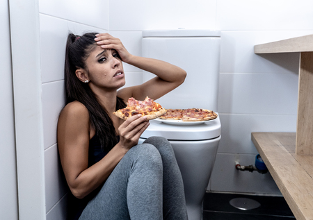 Attractive young and sad bulimic young woman feeling guilty and sick eating while sitting on the floor next to the toilet in eating disorders anorexia and bulimia concept. Imagens