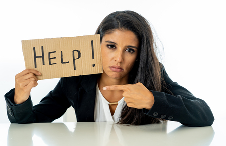 Young beautiful latin business woman overwhelmed and tired holding a help sign. looking Stressed, bored, frustrated, upset and unhappy at work. business frustration concept.
