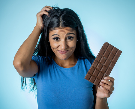 Beautiful young cute and happy latin woman in casual clothes holding big delicious chocolate tablet looking with temptation thinking if ignoring diet and eating sweet junk food isolated background.