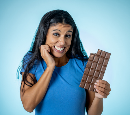 Happy beautiful young latin woman holding a big bar of chocolate with crazy excited face expression in sugar addiction and ignoring diet concept isolated on blue background. Reklamní fotografie