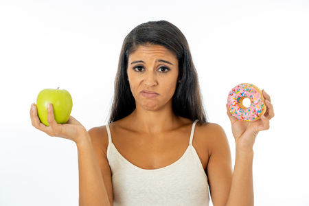 Beautiful young woman tempted having to make choice between apple and doughnut in healthy unhealthy food, detox eating, calories and diet concept.