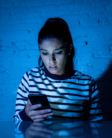 Frightened teenager or young woman using smart mobile cell phone as internet cyberbullying by message stalked abused victim.