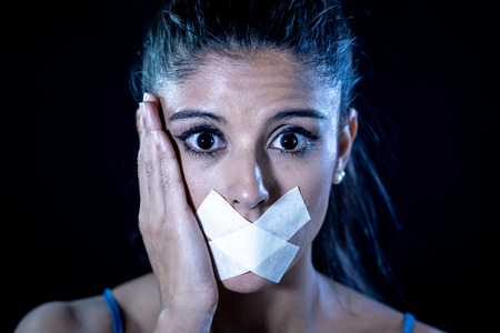 Attractive scared woman with taped mouth making in Silence Abuse Censorship Me too and Freedom of speech Concept Isolated on black background.