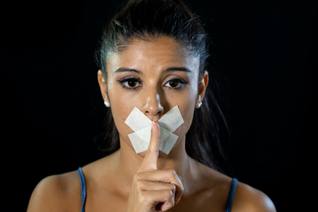 Attractive woman with taped mouth making silence gesture in silence censorship abuse and freedom of speech concept isolated on black background.
