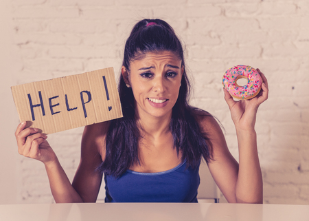 Young worried latin woman feeling tempted and guilty wanting to eat chocolate and donuts asking for help in diet calories sugar addiction nutrition and lifestyle concept. Stock Photo