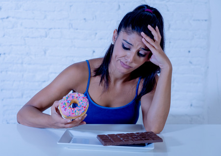 Hungry beautiful young woman unhappy craving sweet chocolate and doughnuts and cannot eat in Dieting Weight loss Sugar addiction Diabetic and unhealthy healthy food concept.