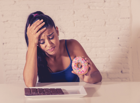 Hungry beautiful young woman unhappy craving sweet chocolate and doughnuts and cannot eat in Dieting Weight loss Sugar addiction Diabetic and unhealthy healthy food concept. Imagens