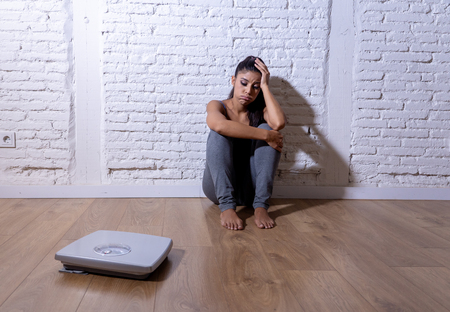 Young anorexic teenager woman sitting alone on ground looking at the scale worried and depressed in dieting and eating disorder concept.