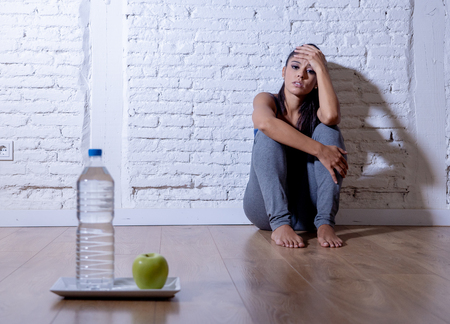Desperate dieting young woman sitting on the ground looking sad at one apple fruit and water as symbol of crazy diet willpower and nutrition disorder.
