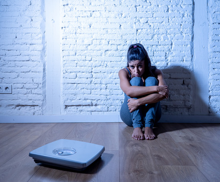 Jonge anorexia boulimische tienervrouw die alleen op de grond zit en naar de schaal kijkt, bezorgd en depressief door een falend dieet en eetstoornisconcept.