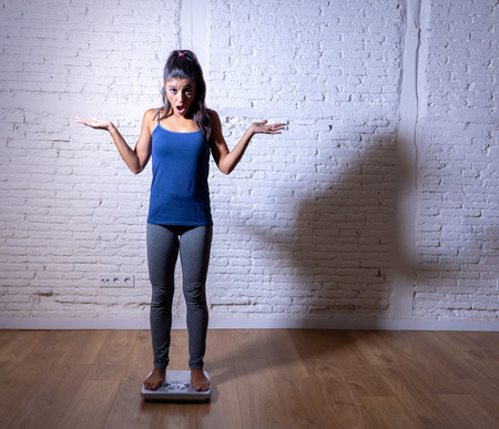 Young fit and slim woman checking body weight on scale finding herself fat and feeling depressed and desperate with big edgy shadow light in eating disorder and dieting concept. Imagens