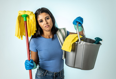 Young beautiful angry and upset housewife woman holding bucket mop cleaning spray feeling sad frustrated and lazy in domestic duties concept isolated on white background.