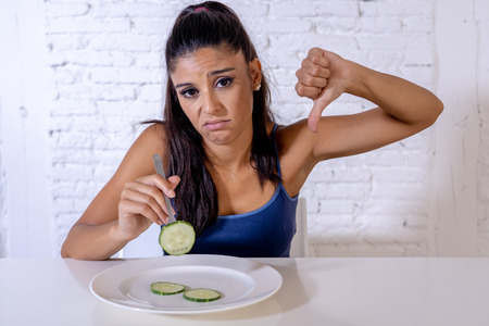 Portrait o f young attractive woman feeling sad and bored with diet not wanting to eat vegetables or healthy food in Dieting Eating Disorders and weight loss concept. Imagens - 110012414