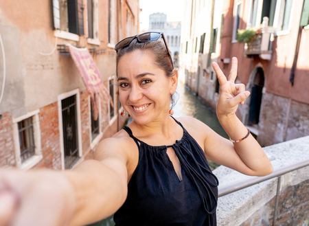 Young attractive latin hispanic tourist taking selfie at venice canal having fun on vacation in Italy in Europe summer travel holiday.
