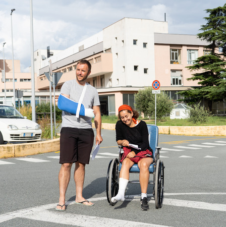 Young injured couple with broken foot and arm coming out of the hospital happy that their insurance paid the medical bills in travel health insurance concept.