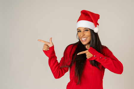 Cheerful beautiful and smiling young woman in santa hat and red sweater smiling playful and holding copy space over gray background in merry christmas happy holidays celebration and sales concept. Stock Photo