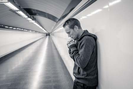 Miserable jobless young man crying Drug addict Homeless in depression stress sitting on ground street subway tunnel looking desperate leaning on wall alone in Mental disorder Emotional pain Sadness. Stock Photo