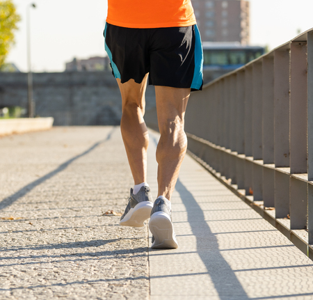 Close up image of strong athletic legs with ripped calf muscle of sport man running at sunset with copy space in urban city training Sport fitness Working out Marathon and healthy life style concept. Stok Fotoğraf - 111756201