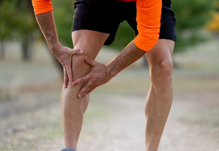 Young fit man holding knee with his hands in pain after suffering muscle injury broken bone leg pain sprain or cramp during a running workout in park outdoors in sport training running injury. Stock Photo