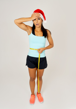 Sad unhappy young latin woman worried of gaining weight after Christmas in consequences of unhealthy eating lifestyle during christmas loss weight and diet isolated on white background. Фото со стока