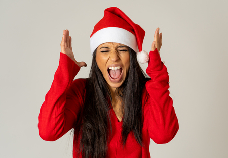 Portrait of a stressed girl wearing red hat looking desperate and angry making gestures isolated on neutral background in christmas is coming not buying present on time overwhelm with family matters.