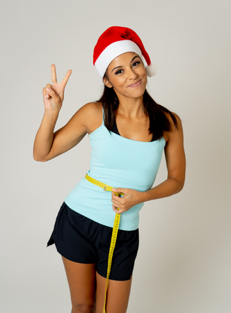 Young attractive latin sport woman in fitness clothes and santa claus Christmas hat holding measure tape on body waist in Wellness diet and weight loss resolution concept isolated on white background.