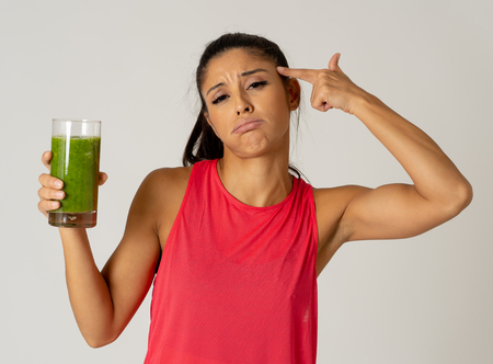 Attractive dieting girl holding detox green juice with angry negative face showing dislike gestures not wanting healthy drink isolated on grey background in healthy food rejection weight loss concept. Imagens