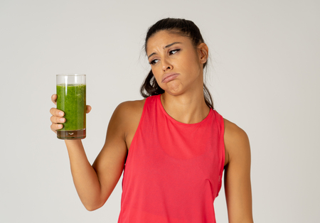Attractive dieting girl holding detox green juice with angry negative face showing dislike gestures not wanting healthy drink isolated on grey background in healthy food rejection weight loss concept. Banco de Imagens