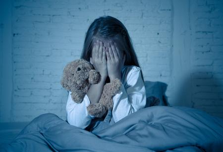 Erschrockenes kleines Mädchen, das im Bett sitzt und ihr Gesicht mit Händen bedeckt, die ihren Teddy aus Angst vor Monstern in der Dunkelheit im Schlafzimmer in der Vorstellung von Albträumen von Kindern und dem Konzept der psychologischen Not halten. Standard-Bild