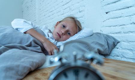 Dolce bambina insonne sdraiata triste a letto guardando la sveglia doversi svegliare ma sentirsi stanca insonne in Problemi a restare addormentati Terrori notturni Disturbo del sonno e concetto di insonnia dei bambini.