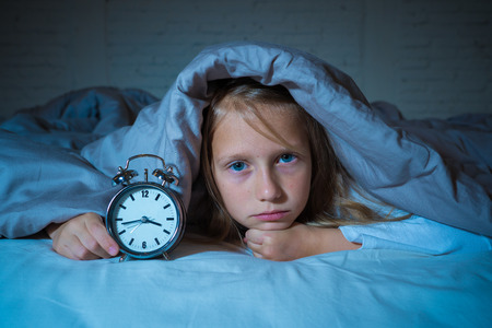 Cute sleepless little girl in bed awake in the middle of the night looking tired having troubles staying asleep at night or waking up too early in Insomnia Anxiety Sleeping Disorders in children.