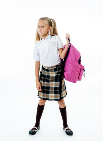 Young tired and sad cute school girl standing with a big heavy school bag on her back on a isolate white background for a back pain stress homework and back to school concept.