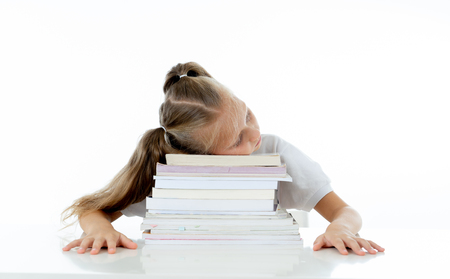 Exhausted sweet cute blonde girl sleeping on a pile of schoolbooks after being studying hard isolated on a withe background in too much learning pressure at school and education concept