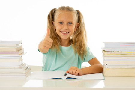 Happy beautiful cute with blond hair little schoolgirl likes studying and reading books in creative education concept with Back to school theme isolated on white background. Stock Photo